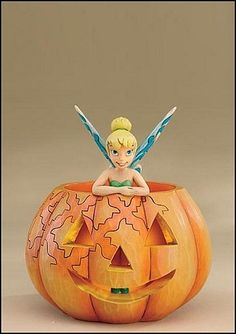 Heartwood Creek by Jim Shore Disney Traditions  A PIXIE TREAT  Tinker Bell has the Halloween spirit in this cute, smiling jack-o-lantern figurine. The inside lights up to give the jack-o-lantern a nighttime glow.  Specifications   Height : 5.5in  Materials : Stone Resin.  Unique variations should be expected; hand painted    Your Price: $37.50