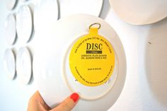 Create a plate display on your wall By applying easy to use adhesive discs from the Container Store and lining up nails on the wall, our project was completed in no time!  Also, just an FYI- should you decide to use Great Grandmother's fine heirloom china… the adhesive discs come right off with soap/water, leaving the dishes perfectly unscathed.