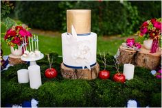 mesa de doces floresta encantada com musgos, maçãs, flores e doces sobre troncos de madeira.
