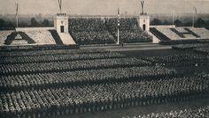 """""""Der Deutsche Gruß"""" im Dritten Reich  Historische Episode: Die HJ hebt zum Deutschen Gruß den Arm. BDM sitzt in weißer Kleidung auf den Tribünen und einige tragen dunkle Blusons mit den Initialen """"A und H"""". Die Gleichschaltung ist vollzogen."""