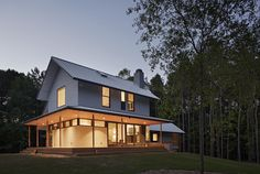 """The main volume presents a traditional front and is wrapped on the west and south by a deep porch,"" says architect Erin Sterling Lewis. ""Living and dining spaces access the porch."" A standing seam metal roof with a Kynar finish and HardiePlank Lap Siding cover the exterior of this 3,000-square-foot home."