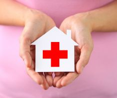 Paper house with red cross stock photo