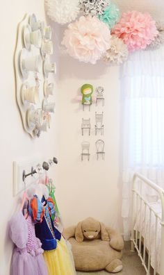 pretty pale pink room with hanging poms and a spot for favourite dress up dresses