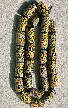 African Trade Beads |  tubular Venetian fancy beads from the late 1800`s used for African trade. | The bodies are black, they are decorated with little rosettes of blue and white swirls circled with yellow.