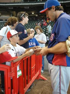 Texas Rangers' Ian Kinsler signs a young fan's baseball before the game (May 19, 2012)