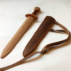 Childrens wooden sword with leather sheath. Toy for a child 4-10 years. It is based on a European medieval sword. The blade and handle are made of