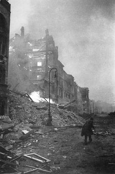 Soviet soldier runs near a burning house during the battle in Berlin.