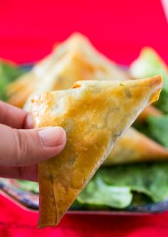 Hand holding baked samosa filled with spinach and feta cheese and cream cheese