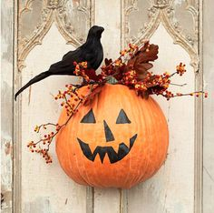 http://www.bhg.com/holidays/?day=12#page=17  Jack-o'-Lantern Door Attendant:   Outfit your door with a friendly face to greet guests. To create this smiling guy, cut an artificial pumpkin in half. Paint a face with black acrylic paint. Decorate with branches and leaves, and top with an artificial crow. Create a wire hanging loop to attach to the top of the pumpkin. Bend it back through the foliage and hang where desired.