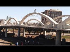Acrobata anda de bicicleta nos arcos de uma ponte