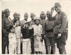 """1937- Japanese officer and soldiers teaching Chinese children to render a """"proper Japanese salute""""."""