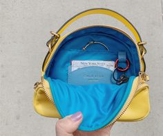 Hand-crafted 4 in 1 small sunrise bag is made to ride different waves throughout our changing day. Real 18 Karat Gold Plated custom designed hardware gives extra sunrise glow. Front compartment has built in phone, lipstick and pen slots. Main compartment has 1 slash pocket with 2 credit card slots and a red floating key ring. On-the-go metro card slot at center back. 4 In 1, Blue Line, Dark Denim, Cowhide Leather, Slot, Custom Design, Sunrise, Waves, Hardware