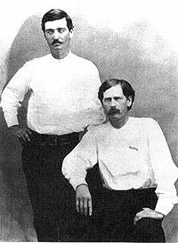 Deputies Bat Masterson (standing) and Wyatt Earp in Dodge City, 1876. The scroll on Earp's chest is a cloth pin-on badge.