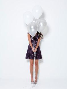 Imagen libre de derechos: Young woman hiding behind balloons at…
