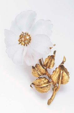 A ROCK CRYSTAL, COLORED DIAMOND AND GOLD BROOCH  Designed as a carved and frosted rock crystal flower, centering upon a circular-cut yellow diamond cluster pistil, extending a sculpted and textured gold stem and leaves, mounted in 18k gold