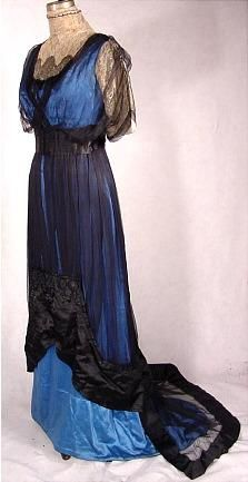 c. 1912 Brilliant Blue Silk Satin Dinner Gown with Black Silk Chiffon and Black Satin Trained Overlay Trimmed with Black Passementerie and Gold Metallic and Ecru Lace