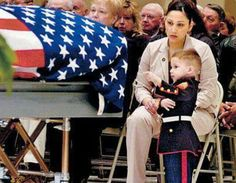 Two-year-old Tyler Miles wearing Marine dress blues and points at the flag-covered casket of his father, Marine Sergeant Sean H. Miles, who was killed in Iraq.