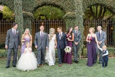 Cute picture of the whole bridal party, groomsmen in grey tux with purple ties and bridesmaids in lavender and purple long semi sweetheart dresses | Monique Hessler Photography | villasiena.cc