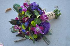 Bridal bouquet with blue, purple, green flowers and peacock feathers.