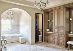 An arched doorway frames a bathtub nook fitted with a spa like tub with a vintage hook and spout tub filler positioned under a window dressed in a damask roman shade beside a white tufted skirted stool placed on brick tiled floors in front of a white wall accented with Ann Sacks Savoy Herringbone Tiles illuminated by a Paris flea market chandelier.
