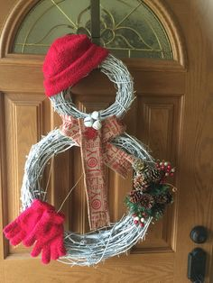DIY Grapevine Snowman Wreath. My twist on a grapevine snowman wreath. First, I spray-painted the wreaths white. Next I tied the two wreaths together with thin jute rope. Lastly, I embellished the snowman with a beanie, some mittens, a scarf and pinecone arrangement