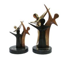 Peça: tridimensional, disponível em 2 tamanhos:  15,5cm e 24,5cm de altura.  Materiais disponíveis: alumínio (prata) e bronze (dourado e patinado).  Base: acrílico preto 11cm de diâmetro x 1cm espessura.  Placa cortesia: aço inox, 6,5x1,5cm.