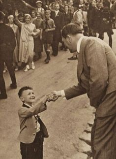 A small boy shaking the hand of Adolf Hitler.