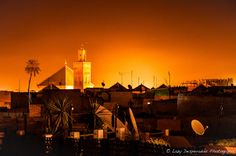 Arabian Rooftops by Lazy Desperados Light at dusk over the rooftops of Marrakech overlooking the mosque all lit up. Great view of the medina.