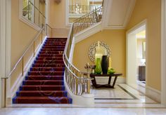 This chic and colorful example of a foyer. The stairs are covered in a red and royal purple carpet with a whimsical pattern. To the right of the staircase is a modern table with vases of different sizes, shapes, and colors.