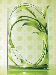 A few calla lilies in a glass container create a super modern centerpiece that doesn't block guest's view