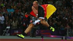 Robert Harting of Germany celebrates by jumping a hurdle after winning gold