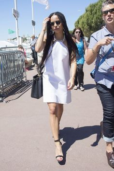 Zoe Kravitz wears a white halter dress with a black handle bag and minimal black sandals