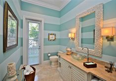 This bathroom matches perfectly with the kids bedroom featuring horizontal stripes and a beach theme.