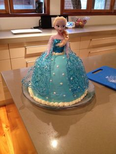 Elsa frozen ice cream cake.  Made using 6l of ice cream, choc ripple biscuits, ice magic and cream.  Used a Pyrex bowl and a cake tin to get the shape.  Sprayed with shimmer spray and added snowflakes.  Piped cream to cover gaps after inserting half a doll.  One very happy 5 year old!