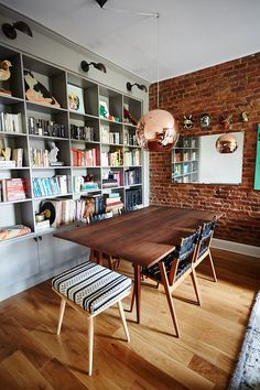 This dining room has exposed brick walls, built-in open shelving with wall sconces above, a wood table with woven chairs, wood flooring and copper globe light fixture.