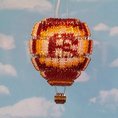 Hand-made hot air balloon lamp in root beer, gold and crystal. It's made from 156 silver safety pins and 1,428 acrylic beads and is designed to hang from a ceiling hook or wall bracket. Uses a 7-watt night light bulb on a 6-foot clip in cord.