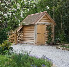 A quaint wooden garden store garden building with attached log store