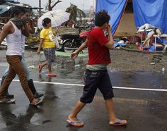 Survivors walk past bodies swept by flood waters after Super Typhoon Haiyan battered Tacloban city in central Philippines