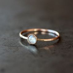 A beautiful, rose cut, white diamond sparkles in a simple 14k yellow gold bezel atop a thin, lightly hammered 14k yellow gold band. The hammering
