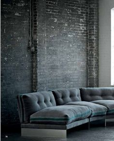 Old brick walls and a sofa in the same tone. Cosy industrial design working with old materials in situ.