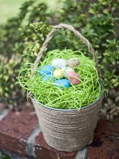 Bring a natural, earthy feel to your Easter celebration with a jute-wrapped basket. Wrap jute or twine, starting from the bottom of a galvanized bucket, and go up along the side and around to the bottom again to create a handle. Continue wrapping the sides of the bucket, occasionally hot gluing to the sides. Continue until entire bucket is wrapped in jute and handles are secure. Fill the bucket with green grass filler and egg-shaped candy.