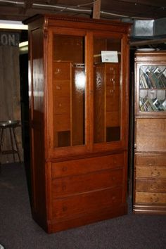 """Very Unusual And All In Orginal Condition! This Mission Gun Cabinet Is Made From Quarter-Sawn Oak. It Will Hold Seven Guns And Has Eight Ammo Or Storage Drawers.  Approx. 83"""" h. x 16"""" d. x 39"""" w.  Item# 9D111  Price $SOLD$"""