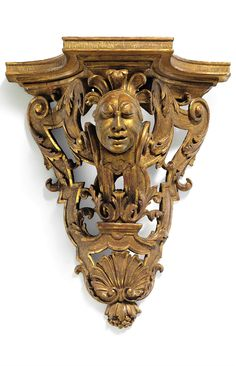 c.1700, A QUEEN ANNE GILTWOOD WALL BRACKET POSSIBLY BY JEAN OR THOMAS PELLETIER. The outset top on openwork support centered by a mask with feathered headdress amidst strapwork and acanthus foliage H: 15 ¼ in. (38.7 cm), W: 12 ¾ in. (32.4 cm), D: 7 ¼ in. (18.4 cm) Wall Brackets, Acanthus, Queen Anne, Headdress, Console, Lion Sculpture, Statue, Antiques, Top