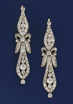 A pair of 18th century silver and paste pendeloque earpendants   Each composed of two colourless paste graduated elongated oval drops with ribbon bow connecting link and beaded detail, circa 1770