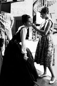 """A makeup touch-up for Audrey Hepburn, during the filming of the classic, """"My…"""
