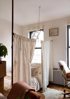 Small Studio Apartment with Curtains Hung from Pipe Conduit