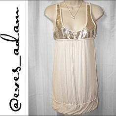 """Ivory and silver sequin accented tank blouse This sequin accented ivory soft tank blouse is so soft and so adorable. Made of 95% poly, 5% spandex. This is preloved but very good condition. No visible signs of staining and comes from a very clean smoke free home. There are about three mini sequins missing from the top but I didn't even notice them until I inspected the shirt thoroughly. Approx 29"""" long Forever 21 Tops"""