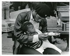 A a member of The Black Panther Party for Self Defense feeds his son at a Free Huey rally on February 17, 1968.