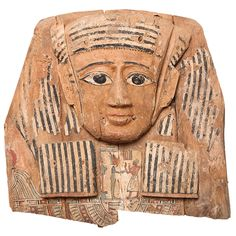 Large Egyptian Wood Carved and Painted Sarcophagus Mask       Large Egyptian Wood Carved and Painted Sarcophagus Mask     0  The mask with polychrome painted gesso details, shown wearing a striped black and white wig, the face carved with exaggerated features, painted between the lapels with the deceased, standing before Osiris, with an udjat eye below and remains of a broad collar with falcon head terminal,