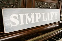 "DIY ""Simplify"" sign -- cut letters in self-adhesive shelf liner, stick on sign, paint inside letters. Let paint dry, peel off shelf liner, lightly sand surface & edges to distress."
